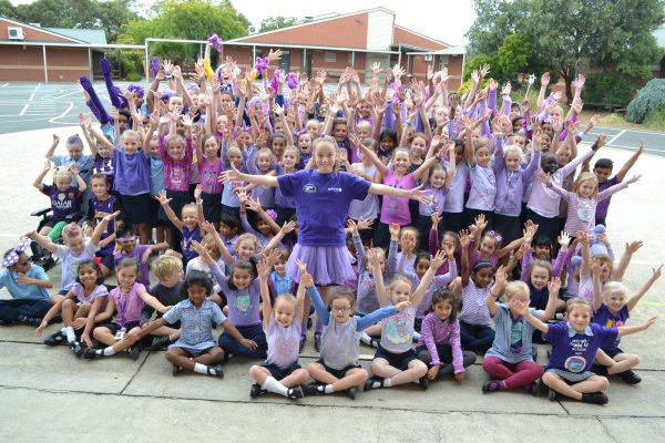 Large group of school children dressed in purple with arms raised