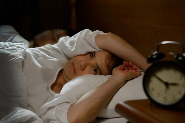 Woman awake in bed alarm clock next to bed