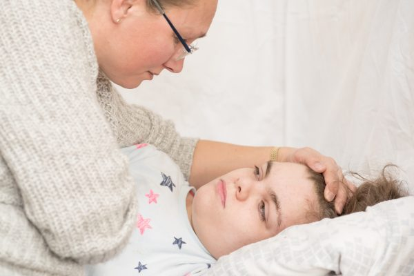 Mother leaning over to comfort girl in bed
