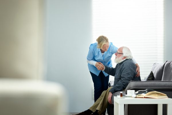 Woman assisting older man in aged care home
