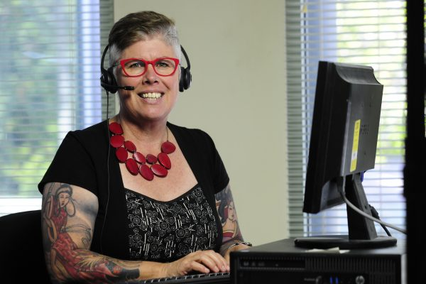 Epilepsy support worker with headphones working at computer